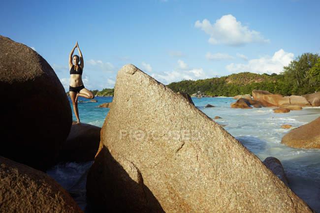 Seychellen, Frau steht auf einem Felsen und macht Yoga-Übungen — Stockfoto