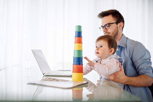 Jeune homme avec bébé fille sur ses genoux assis au bureau — Photo de stock