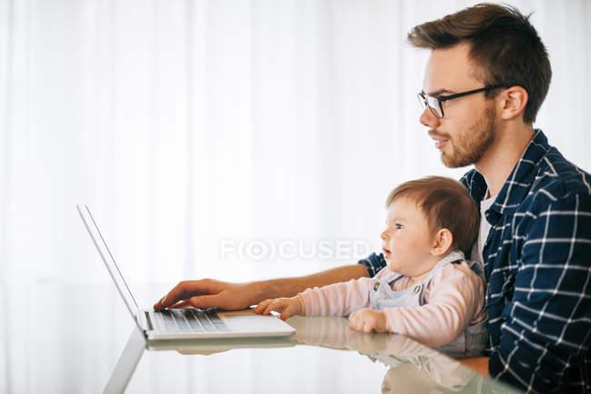 Молода людина з дитини дівчина на колінах, намагаючись працювати — стокове фото