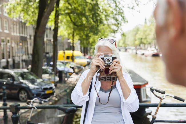 Pays-Bas, Amsterdam, femme âgée prenant une photo avec caméra analogique au canal de la ville — Photo de stock
