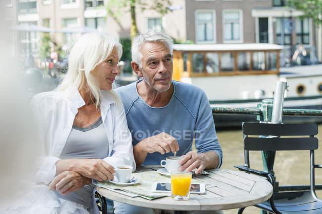 Pareja senior, Países Bajos, Amsterdam, en un café al aire libre - foto de stock