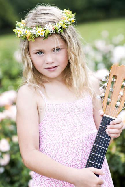 Девушка с гитарой в цветочном венке — стоковое фото