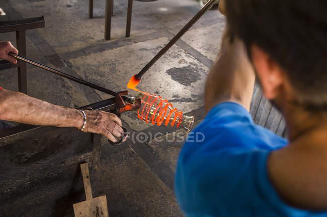 Мужчины, работающие с расплавленным стеклом на стекольном заводе — стоковое фото