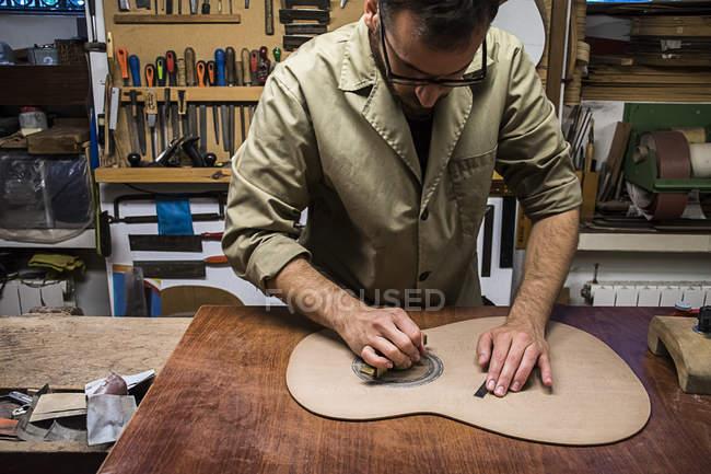 Лютье изготавливает гитару в своей мастерской — стоковое фото