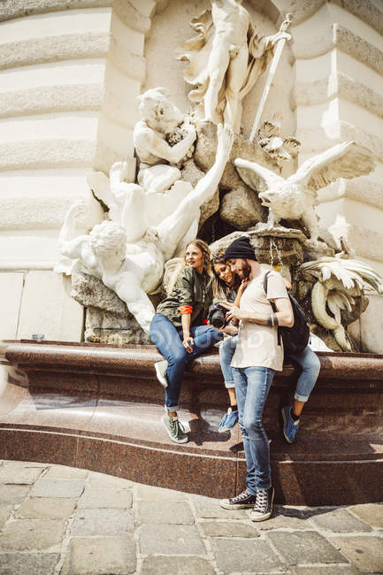 Austria, Vienna, group of three friends with camera in front of fountain at Hofburg Palace — Stock Photo