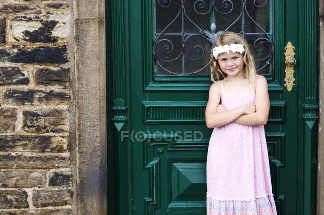 Дівчина стояла перед старих вхідних дверей — стокове фото