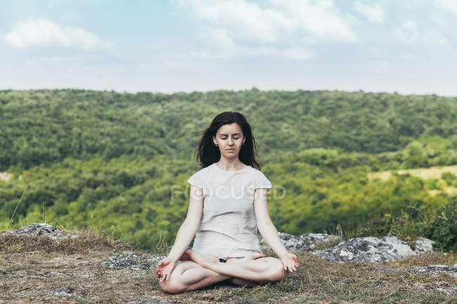 Young woman meditating on the cliff — Stock Photo