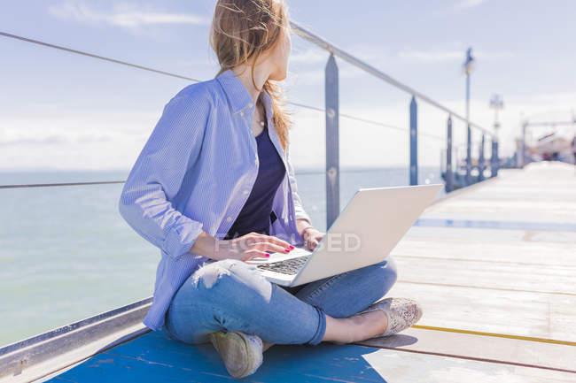 Frau benutzt Laptop auf Steg mit Meer im Hintergrund — Stockfoto