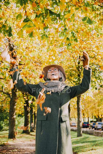 Mulher jogando folhas de outono no ar — Fotografia de Stock