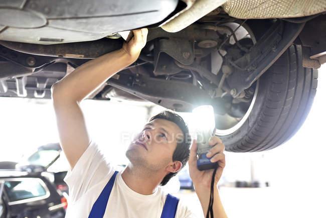 Механік вивчення днища автомобіля в гаражі — стокове фото