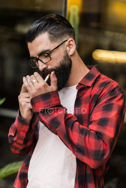 Hipster with cigarette standing in front of bar — Stock Photo