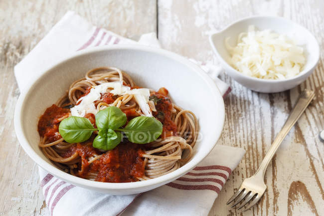 Bowl with spelt whole grain spaghetti, tomato sauce, parmesan and basil — Stock Photo