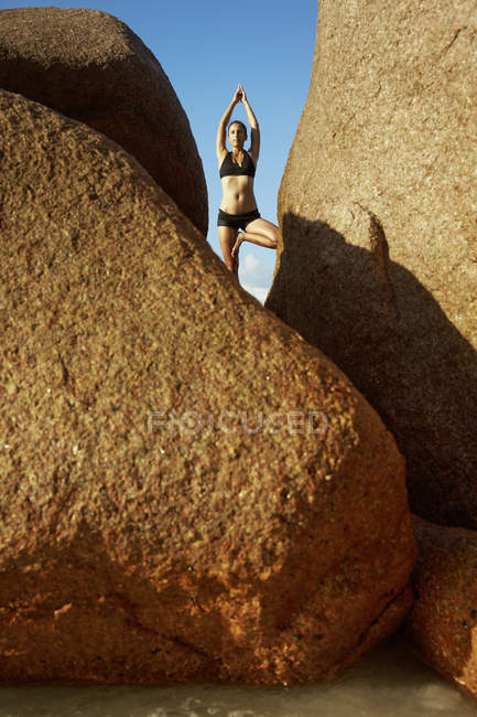 Seychelles, woman standing on a rock doing yoga exercise — Stock Photo