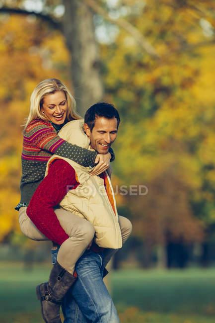 Uomo dando la sua ragazza a cavalluccio nel parco autunnale — Foto stock