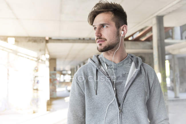 Athletic man with earbuds standing in underpass — Stock Photo