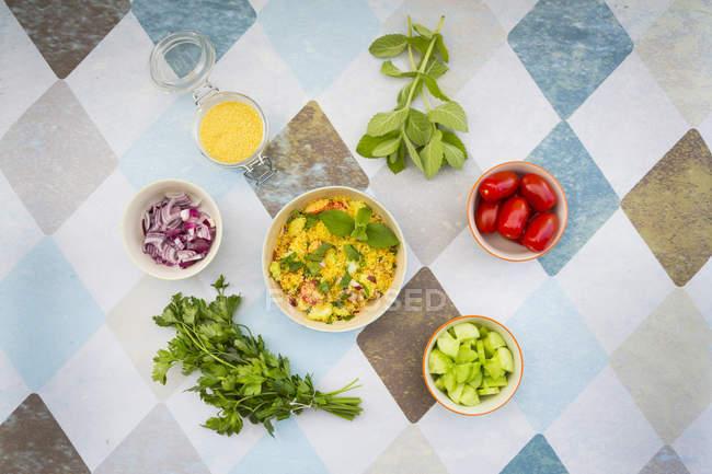 Ciotola di insalata di cous cous preparato con gli ingredienti — Foto stock