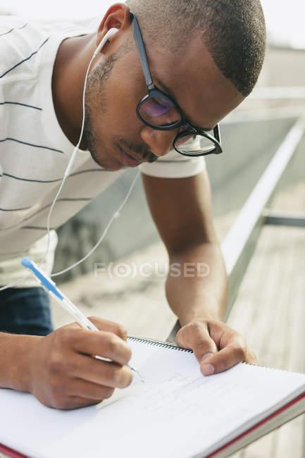 Studente che scrive nel quaderno — Foto stock