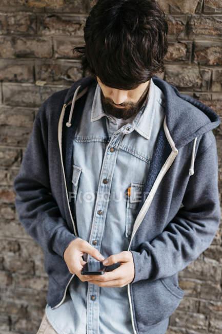 Junger Mann mit seinem smartphone — Stockfoto