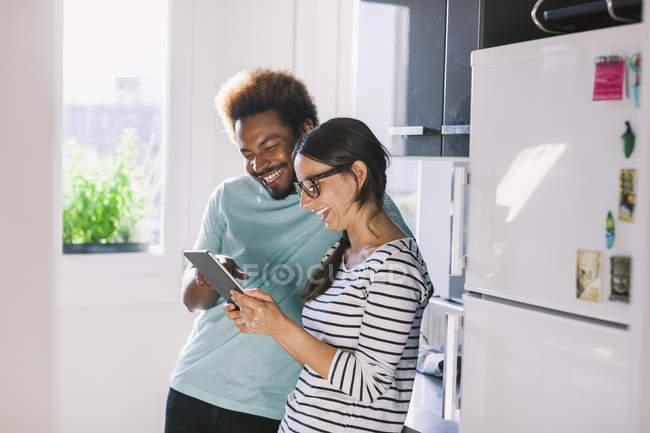 Happy young couple having fun in their kitchen — Stock Photo