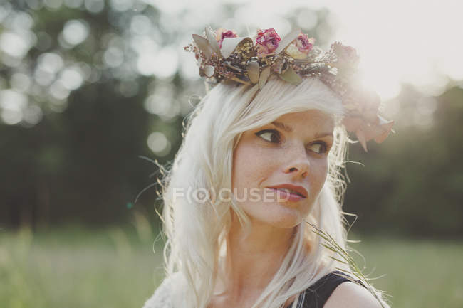 Girl with flowers in her hair during sunset — Stock Photo