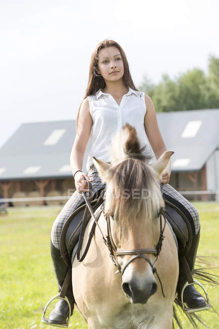 Portrait of teenage girl riding on a horse — Stock Photo