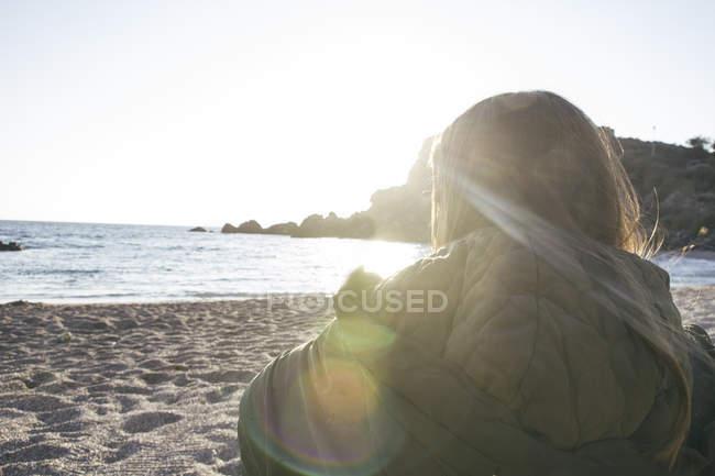 Молода жінка на пляжі, дивлячись на морі — стокове фото