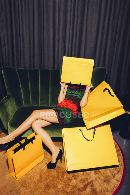Young woman sitting on couch hiding her face behind a yellow shopping bag — Stock Photo