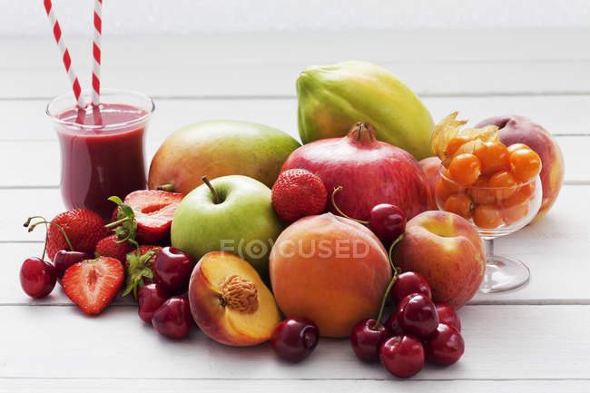Different fruits and glass of strawberry smoothie on white surface — Stock Photo