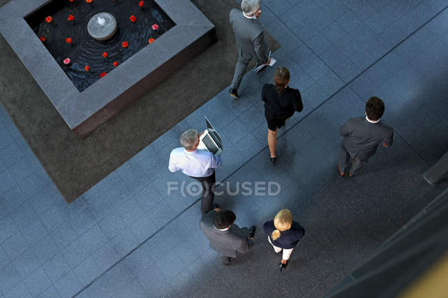 Top view of businesspeople walking through lobby — Stock Photo