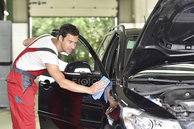 Man wearing professional uniform polishing car — Stock Photo
