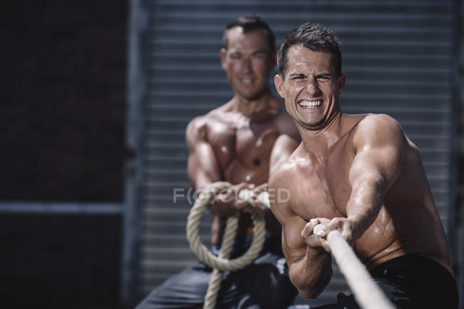 Deux athlètes CrossFit tirant ensemble la corde — Photo de stock
