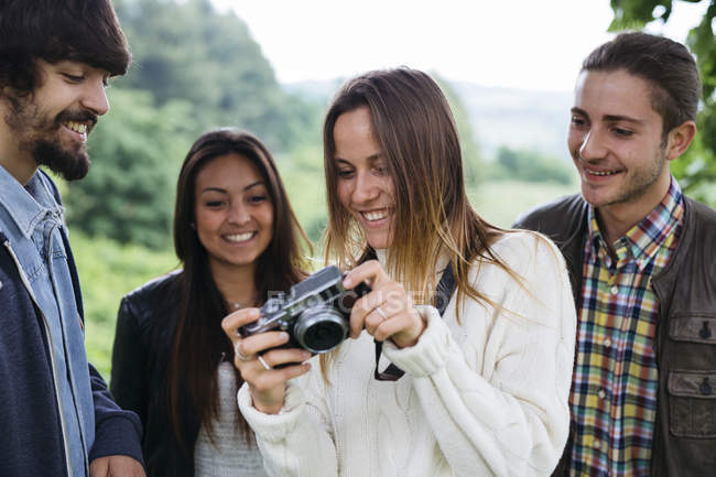 Four friends sharing camera in nature — Stock Photo