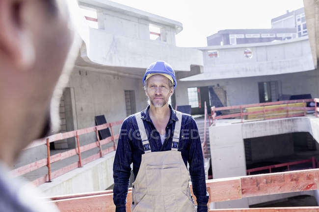 Confident man with hard hat with colleague on construction site — Stock Photo