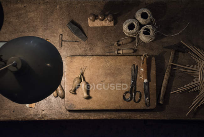 Tools and twine rolls on a wood table in a workshop — Stock Photo