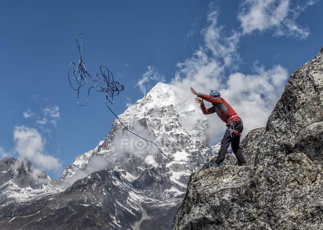 Nepal, Himalaya, Solo Khumbu, Ama Dablam, man standing on rock throwing rope — Stock Photo