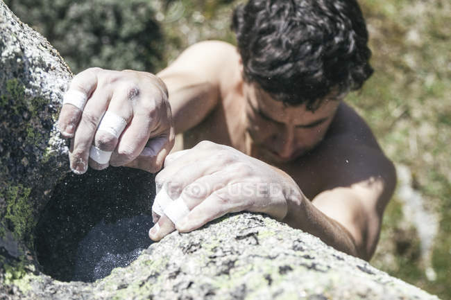 Hands of climber with sticking plaster and chalk during a boulder climbing — Stock Photo