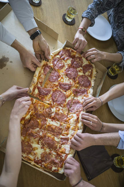 Cropped image of colleagues in office sharing pizza — Stock Photo