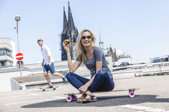 Germany, Cologne, portrait of young woman with bagel sitting on skateboard — Stock Photo