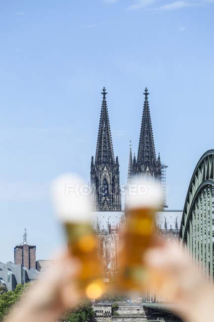 Allemagne, Cologne, deux toasts avec des verres Koelsch devant la cathédrale de Cologne — Photo de stock