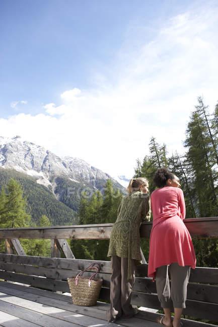 Швейцария, две молодые женщины, стоящие на террасе, глядя на вид — стоковое фото