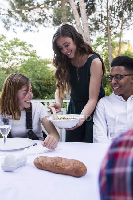 Женщина, подающая табуле своим гостям во время летнего ужина — стоковое фото