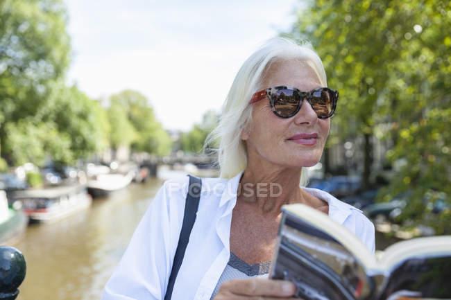 Нидерланды, Амстердам, пожилая женщина читает экскурсию по городскому каналу — стоковое фото