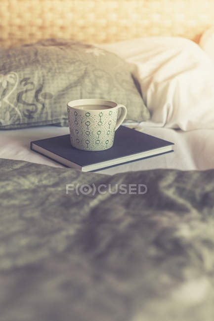 Book and cup of white coffee on a bed — Stock Photo