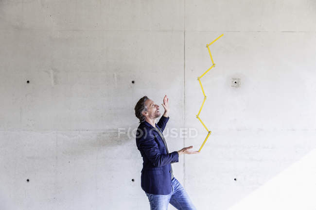 Mann balanciert Poet-Regel vor Betonwand — Stockfoto