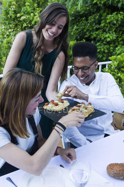 Woman offering focaccia to her guests during a summer dinner — Stock Photo