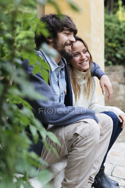 Щасливі молоді пари сидять рука об руку, відпочиваючі — стокове фото