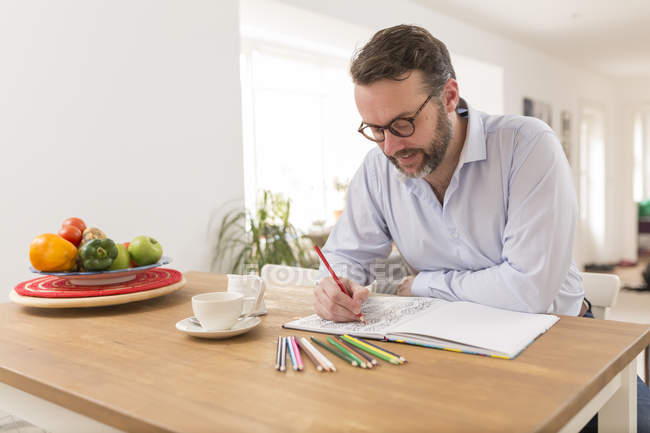 Man with colouring book and coloured pencils sitting at wooden table — Stock Photo