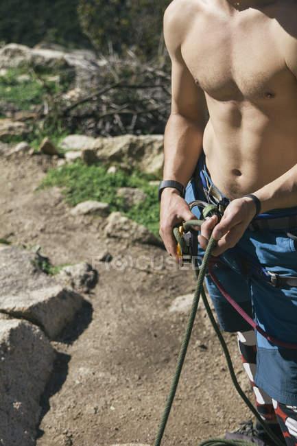 Без рубашки альпинист закрепляется во время восхождения — стоковое фото