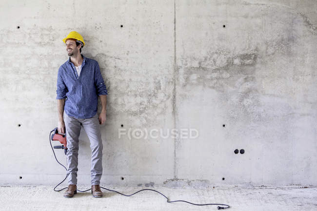 Smiling man with hard hat on construction site holding drill — Stock Photo