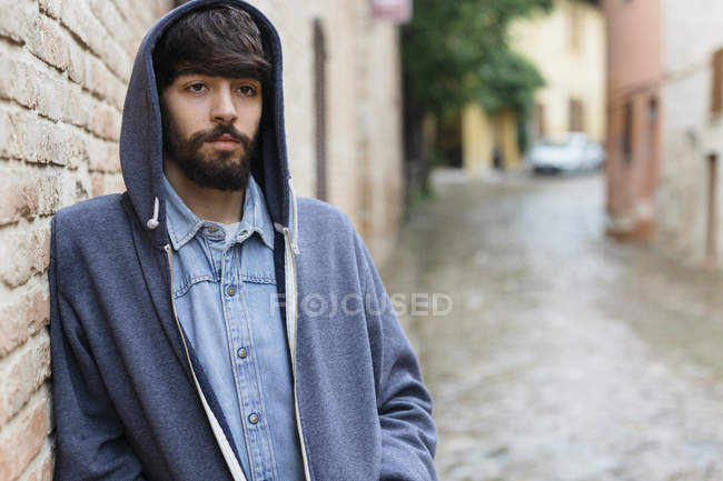 Italy, San Gimignano, portrait of pensive young man wearing hooded jacket — Stock Photo